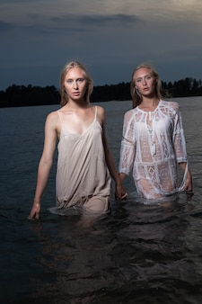 Zwei junge zwillingsschwestern mit langen blonden haaren, die in hellen kleidern im wasser des sees in der sommernacht aufwerfen und kamera betrachten