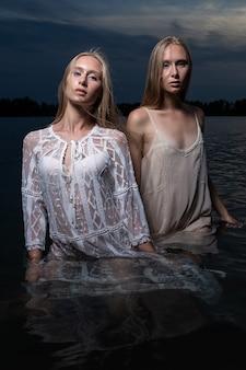 Zwei junge zwillingsschwestern mit langen blonden haaren, die in hellen kleidern im wasser des sees in der sommernacht aufwerfen