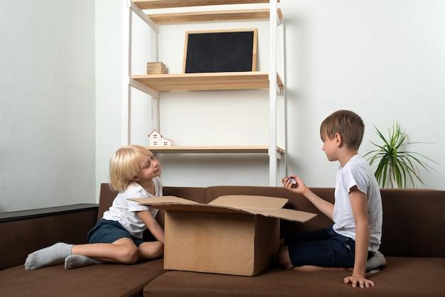 Zwei jungen auf der couch öffneten eine große kiste. kinder öffneten das geschenk.