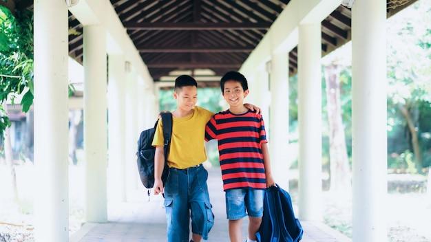 Zwei jungen der grundschule mit schultaschen hinter dem rücken.