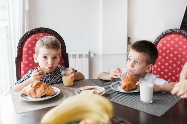 Zwei jungen, die am morgen frühstücken