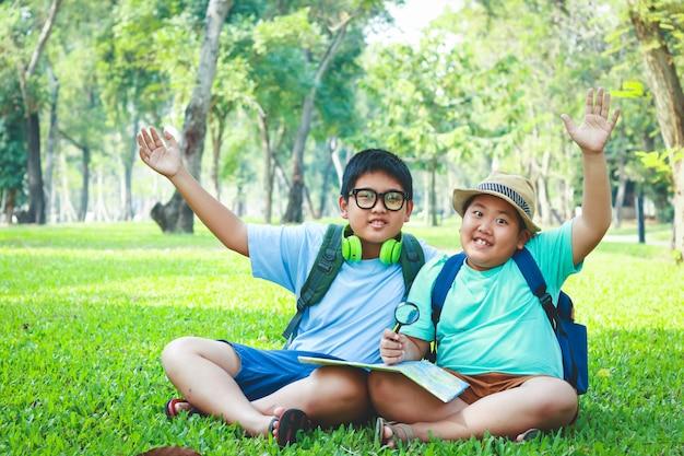 Zwei jungen, die an der natürlichen karte sitzen