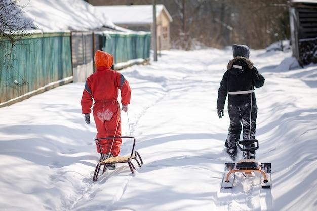 Zwei jungen, die auf schneebedeckte straße im dorf gehen