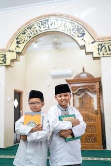 Zwei jungen, die den heiligen koran halten