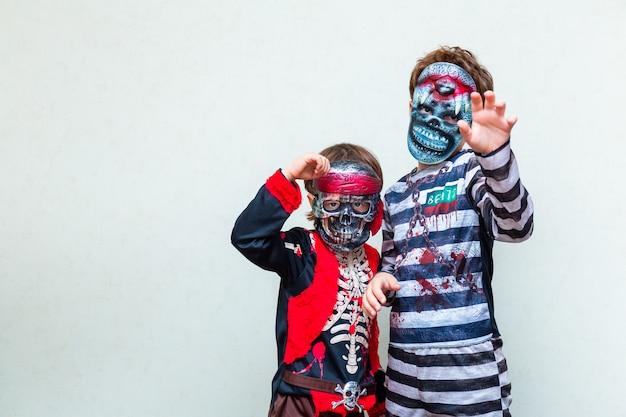 Zwei jungen, die ein gruseliges kostüm mit masken auf hellem hintergrund tragen, kopierraum. kinder bereiten sich im oktober auf die halloween-party vor.