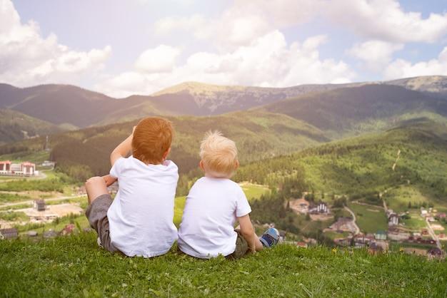 Zwei jungen, die einen hügel sitzen und die berge betrachten. rückansicht