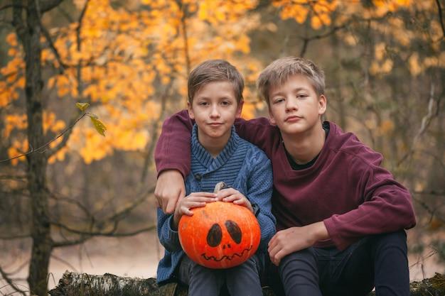Zwei jungen, die einen kürbis halten. das konzept der ferien. vorbereitung auf halloween. ernte.