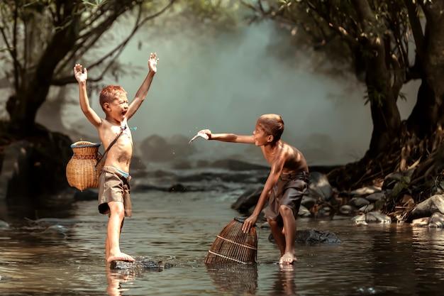 Zwei jungen, die fische in einem strom nahe dem haus in den ländlichen gebieten von thailand fangen