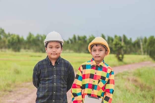 Zwei jungen, die helmingenieur tragen tablette im freien stehen tragen