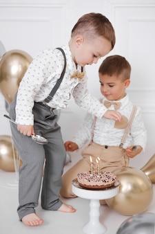 Zwei jungen feiern geburtstag, kinder haben eine b-day-party. geburtstagstorte mit kerzen und luftballons. fröhliche kinder essen kuchen, feiern, weißes minimalistisches interieur.
