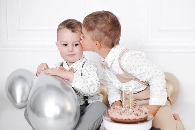 Zwei jungen feiern geburtstag, kinder haben eine b-day-party. geburtstagstorte mit kerzen und luftballons. glückliche kinder, feiern, weißes minimalistisches interieur.