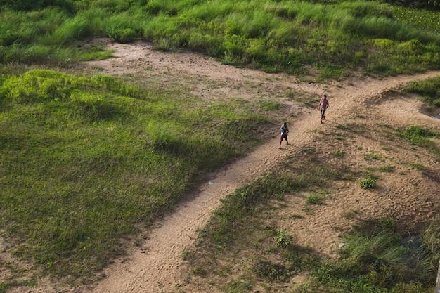 Zwei jungen gehen hinunter zum fluss