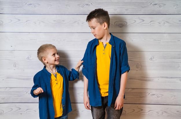 Zwei jungen in freizeitkleidung aus weißem holz schauen sich an