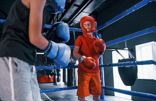 Zwei jungen in schutzausrüstung haben sparring und kämpfe auf dem boxring.