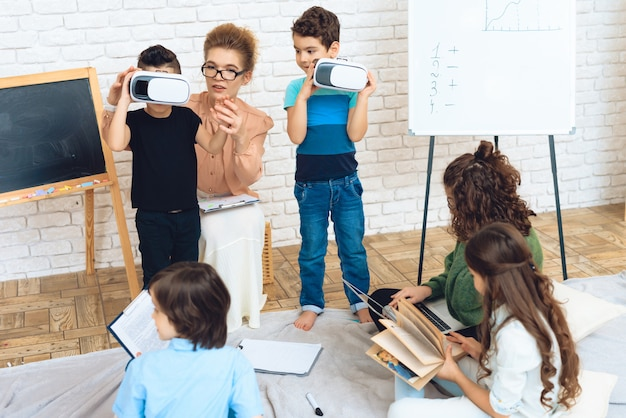 Zwei jungen lernen im klassenzimmer die technik der vr kennen.