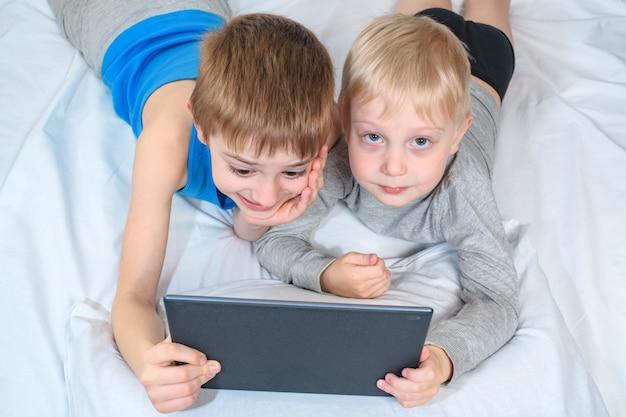Zwei jungen liegen im bett und betrachten die tablette. freizeitgeräte