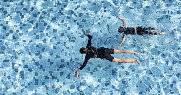 Zwei jungen lustiges schwimmen zusammen im klaren wasserpool, aus der vogelperspektive genommen.