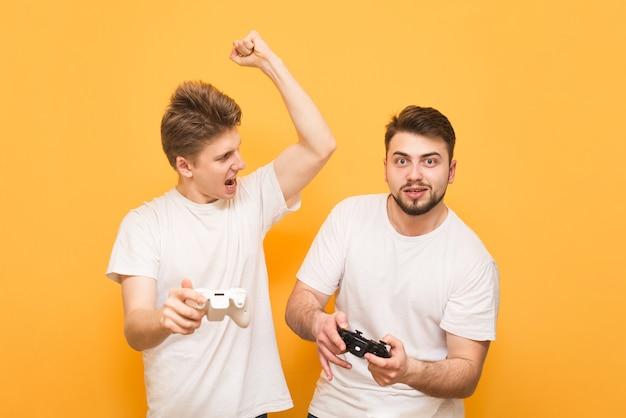 Zwei jungen mit joysticks in den händen sind gelb und spielen auf der konsole