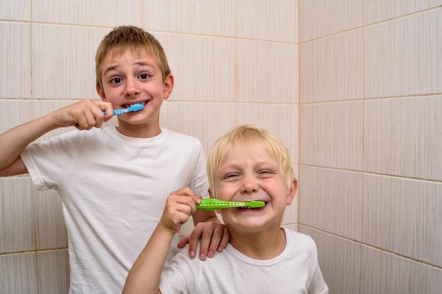 Zwei jungen putzen sich im badezimmer gründlich die zähne