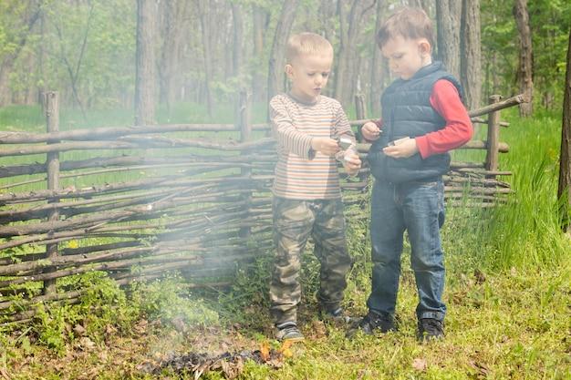 Zwei jungen spielen neben einem rauchenden feuer