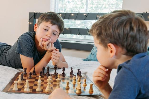 Zwei jungen spielen zu hause schach auf dem bett kinder üben ein brettspiel