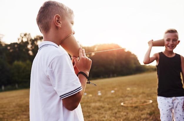 Zwei jungen stehen auf dem feld und sprechen mit einer schnur kann telefonieren.