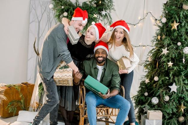 Zwei jungen und zwei mädchen feiern weihnachten in einem dekorierten gemütlichen raum, der geschenkboxen hält