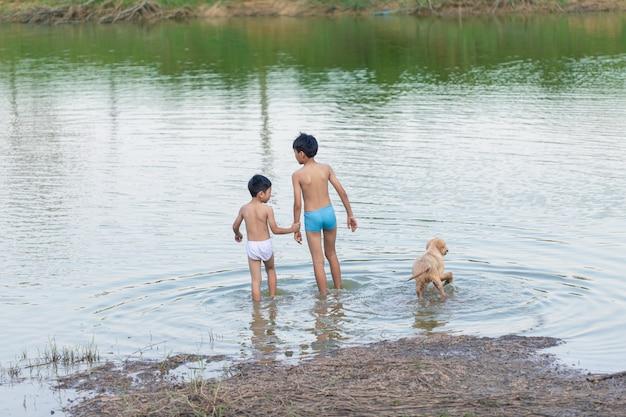 Zwei jungen unterschiedlichen alters und hunde gehen im fluss schwimmen