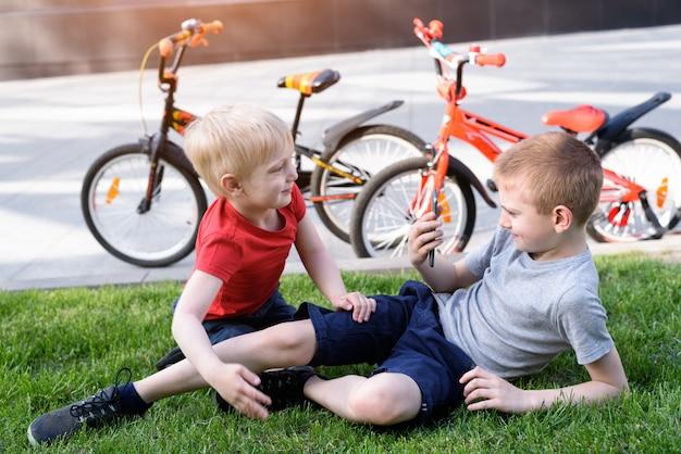 Zwei jungen werden auf einem smartphone fotografiert, während sie auf dem gras sitzen. erholung nach dem radfahren, fahrräder im hintergrund
