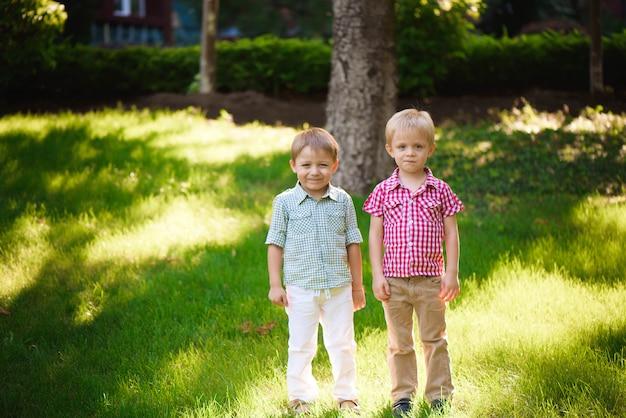 Zwei jungenbrüder, die draußen in einen park spielen und springen.