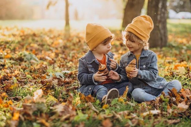 Zwei jungenbrüder sitzen auf gras im park und essen croissants