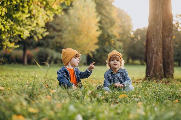 Zwei jungenbrüder sitzen auf gras unter dem baum