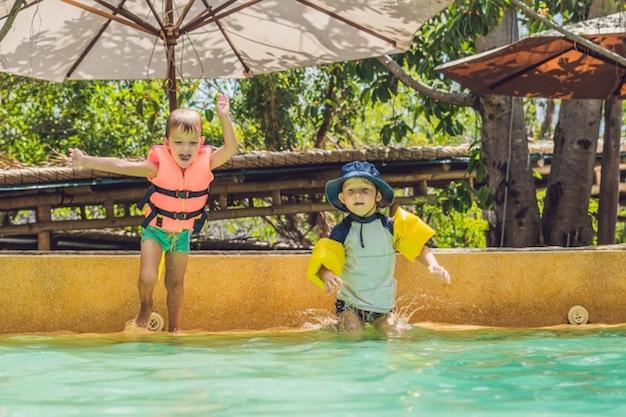 Zwei jungenfreunde, die in den pool springen