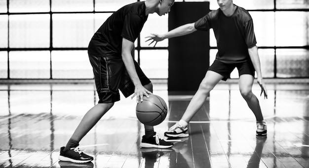 Zwei jungs im teenageralter spielen zusammen basketball auf dem platz