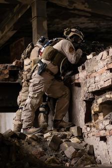 Zwei jungs in amerikanischen militäruniformen stehen auf steinen in einem baufälligen gebäude
