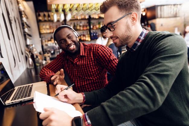 Zwei jungs sitzen mit einem computer an der bar.