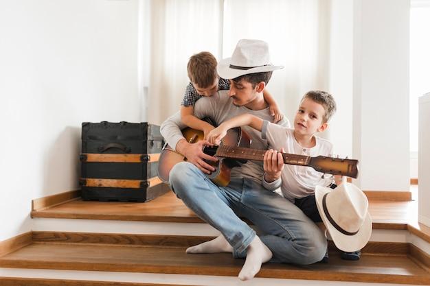 Zwei jungs sitzen mit ihrem vater gitarre spielen
