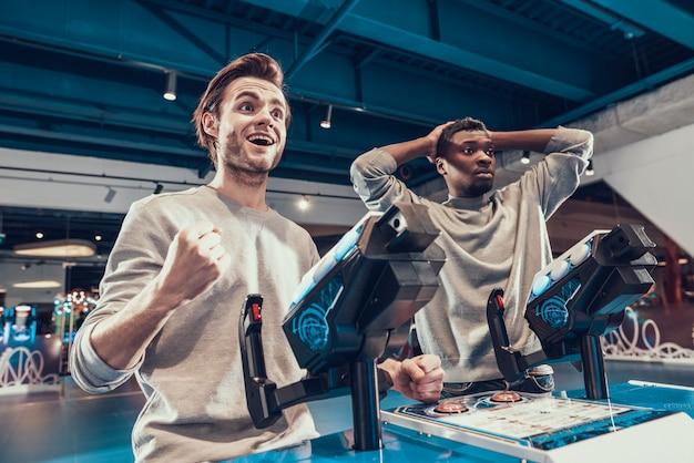 Zwei jungs steuern blaue raumschiffe in einer spielhalle