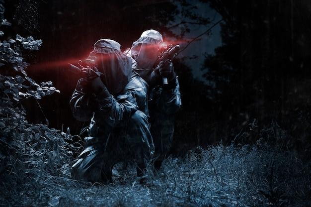 Zwei kämpfer einer spezialeinheit bewegen sich nachts durch den wald. das konzept der spezialoperationen, nato, krieg. gemischte medien