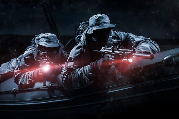 Zwei kämpfer einer spezialeinheit bewegen sich nachts in einem boot auf dem fluss. das konzept der spezialoperationen, nato, krieg. gemischte medien