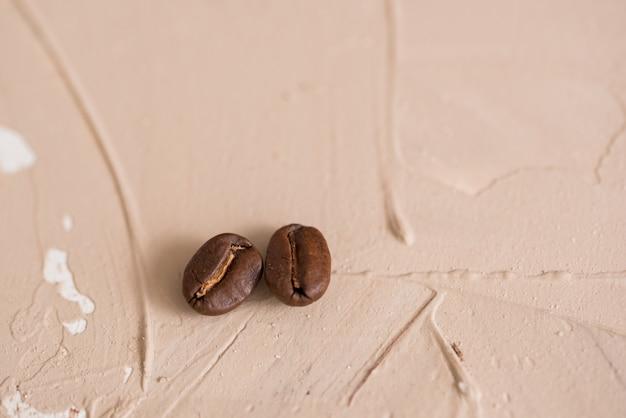 Zwei kaffeebohnen auf konkretem braunem rosa weinlesehintergrund