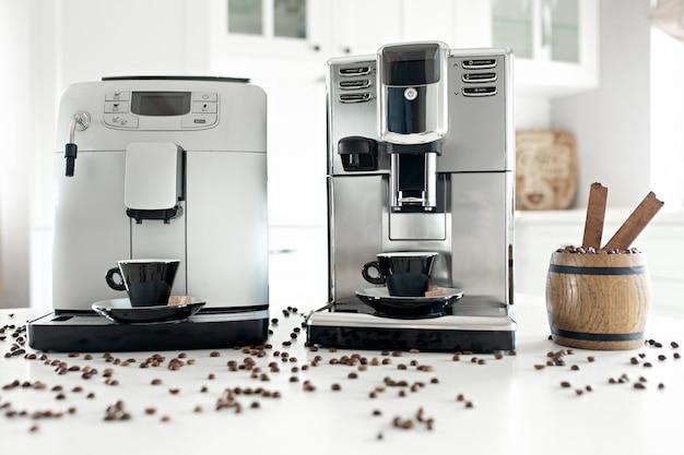 Zwei kaffeemaschinen in der hauptküche mit einem hölzernen behälter mit kaffeebohnen.