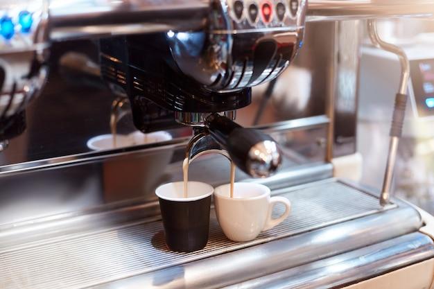 Zwei kaffeetassen auf kaffeemaschine