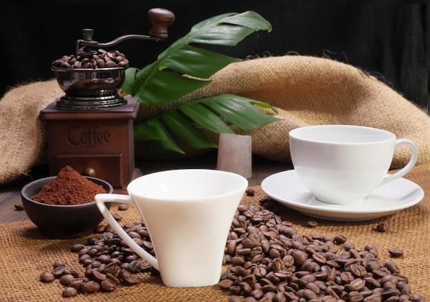 Zwei kaffeetassen, gemahlener kaffee, geröstete kaffeebohnen, mühle und monstera stehen auf holztisch mit sackleinenhintergrund