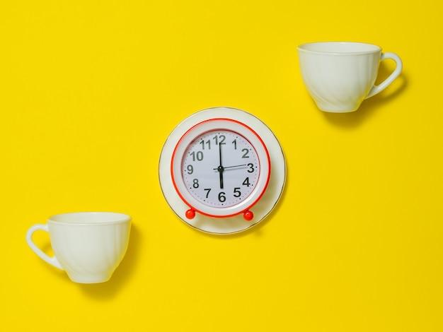 Zwei kaffeetassen und ein roter wecker auf einer weißen untertasse auf gelbem grund. das konzept, den ton am morgen anzuheben. flach liegen.