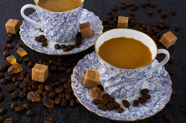 Zwei kaffeetassen und kaffeebohnen auf schwarzem hintergrund