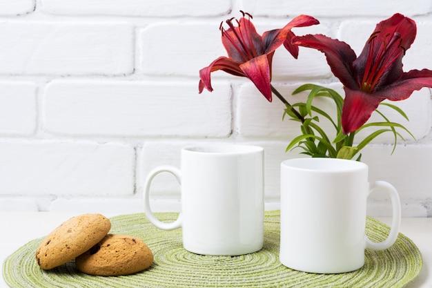 Zwei kaffeetassenmodell mit roter lilie und coockie