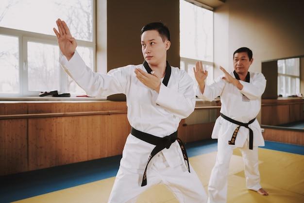 Zwei kampfkunststudenten, die karatepositionen tuend ausbilden.