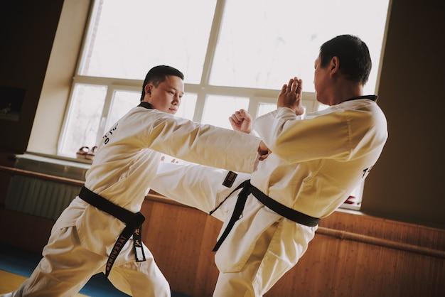 Zwei kampfkunststudenten im weißen sparring zusammen.