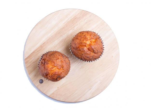 Zwei karottenmuffins auf dem hölzernen küchenbrett lokalisiert auf weiß